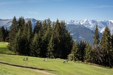 Golf course in Verbier between trees and mountains
